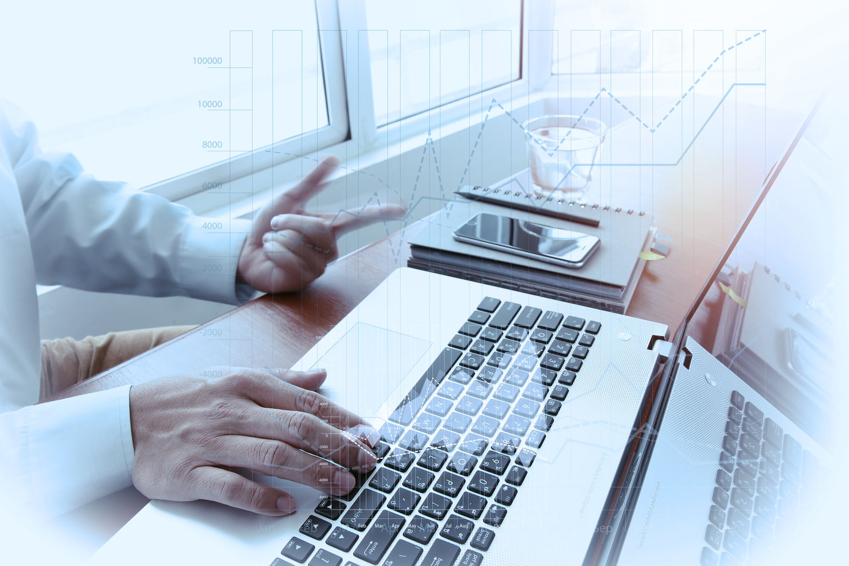 business documents on office table with smart phone and digital tablet and graph business diagram and man working in the background with business graph diagram